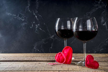 Valentines day with red roses and heart shaped chocolates and wine in glasses on wooden table. Copy space for your text