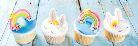 Easter holiday greeting card background. Cute homemade cupcakes with traditional Easter bunny, egg and springtime flowers decor. Happy easter concept. Copy space for your text Stock Photo