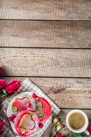 Valentine day brunch food recipe idea. Delicious homemade heart shaped red and white pancakes with berries. Concept of a festive breakfast for Valentine's Day, pleasant surprise for loved one
