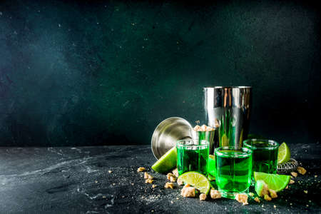 Strong alcohol. Absinthe with sugar, ice cubes and lime slices, Three shot glasses with absinthe. Dark stone background copy space Banque d'images - 138395456