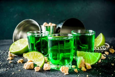 Strong alcohol. Absinthe with sugar, ice cubes and lime slices, Three shot glasses with absinthe. Dark stone background copy space Banque d'images - 138395501