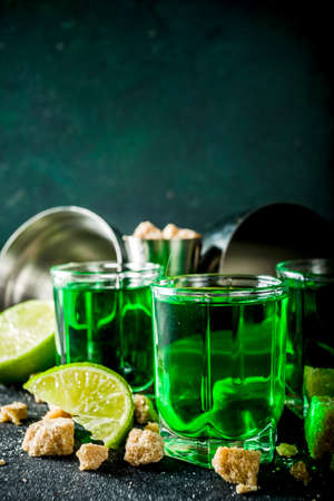 Strong alcohol. Absinthe with sugar, ice cubes and lime slices, Three shot glasses with absinthe. Dark stone background copy space Banque d'images - 138395530