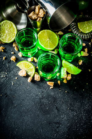 Strong alcohol. Absinthe with sugar, ice cubes and lime slices, Three shot glasses with absinthe. Dark stone background copy space Banque d'images - 138395467