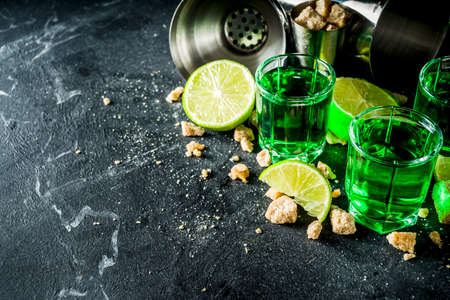 Strong alcohol. Absinthe with sugar, ice cubes and lime slices, Three shot glasses with absinthe. Dark stone background copy space Banque d'images - 138395601