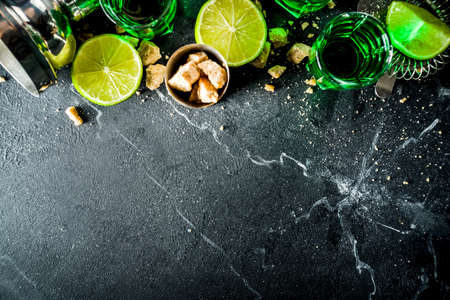 Strong alcohol. Absinthe with sugar, ice cubes and lime slices, Three shot glasses with absinthe. Dark stone background copy space Banque d'images - 138395645