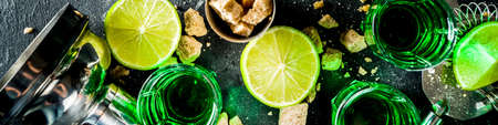 Strong alcohol. Absinthe with sugar, ice cubes and lime slices, Three shot glasses with absinthe. Dark stone background copy space Banque d'images - 138395643