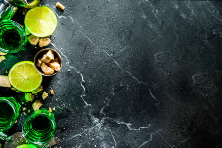 Strong alcohol. Absinthe with sugar, ice cubes and lime slices, Three shot glasses with absinthe. Dark stone background copy space Banque d'images - 138395646