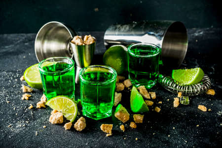 Strong alcohol. Absinthe with sugar, ice cubes and lime slices, Three shot glasses with absinthe. Dark stone background copy space Banque d'images - 138395664