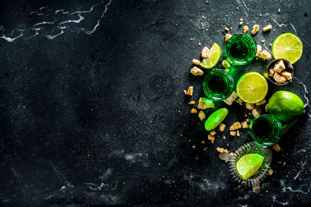 Strong alcohol. Absinthe with sugar, ice cubes and lime slices, Three shot glasses with absinthe. Dark stone background copy space Banque d'images - 138395705