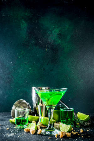 Strong alcohol cocktail. Absinth and vodka martini drink with sugar, ice cubes and lime, With ingredients, barmen utensils and shot glasses with absinthe. Dark stone background copy space Banque d'images - 138395541