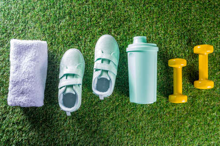 Summer sport, fitness, active lifestyle concept. Pastel sneakers, shaker for cocktail or water, towel, dumbbells. Fitness accessories for summer sport on green grass background flatlay copy space