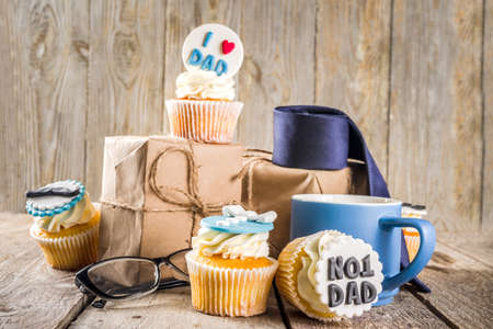 Happy Father's Day greeting card. Greetings and presents for Dad's day - gift box, coffee tea cup, tie, homemade special cupcakes.