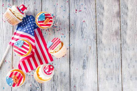 Onafhankelijkheidsdag 4 juli gefeliciteerd achtergrond. Veteranendag. Amerikaanse grondwet vakantie. USA Amerikaanse traditie wenskaart. Patriottische huiscupcakes met decor van Amerikaanse symbolen Stockfoto