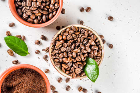 Small bowl of ground coffee and roasted coffee beans on white background, top view 版權商用圖片