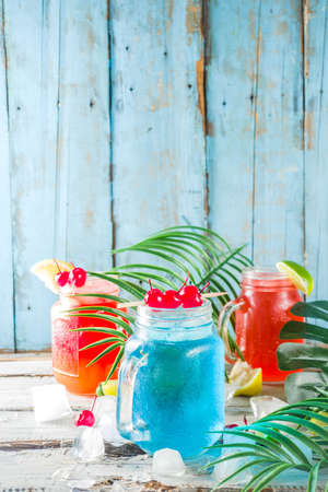 Summer tropical cold drinks. Blue Hawaiian, Tequila sunrise, Sea breeze cocktails over light blue wooden beach background, copy space Reklamní fotografie