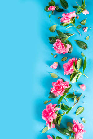 Floral pattern made of pink spring flowers, green leaves, branches on turquoise, aquamarine background. Flat lay, top view. Spring holiday background