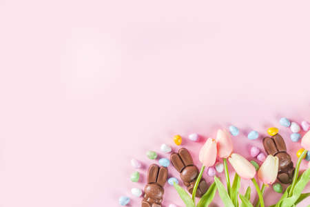 Easter composition with chocolate eggs and bunny rabbits, flat lay copy space