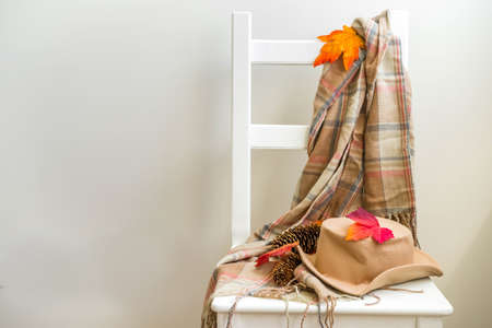 Autumnal cozy mood concept. Home interior, warm clothes, sweater, plaid, scarf, hat with autumn leaves on a white chair. Against the background of a white wall, banner, background copy space