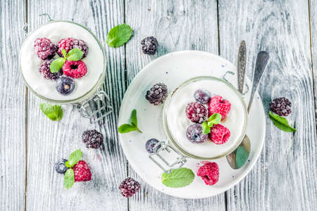 Recipe ideas for summer diet breakfast, healthy morning dessert Cheesecake in portioned jars with summer berries - raspberry, blueberry, blackberry. On wooden background copy space