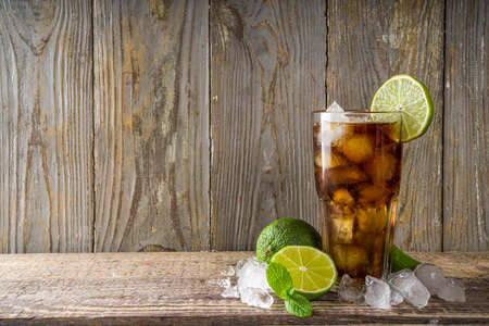 Summer iced alcohol drink with cola and lime. Rum and cola Cuba Libre cocktail. One long glass on wooden background copy space