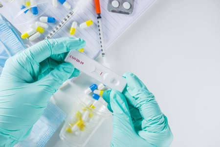 Worldwide coronavirus epidemic concept. Pandemic COVID-19, 2019-nCoV. Laboratory test strip for antibody or sars-cov-2 virus disease. In doctor hands. With pills, vaccination syringes, notebook. Stock Photo