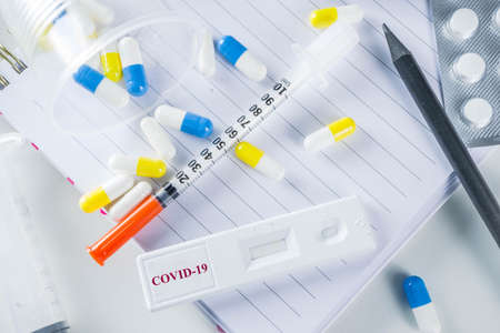 Worldwide coronavirus epidemic concept. Pandemic COVID-19, 2019-nCoV. Laboratory test strip for antibody or sars-cov-2 virus disease. In doctor hands. With pills, vaccination syringes, notebook.