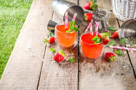 Red summer drink with ice, cold strawberry mojito or lemonade with fresh strawberries and mint on sunlight summer wooden and glass background, copy space Reklamní fotografie