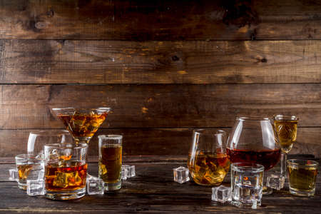 Assortment various hard and strong alcoholic drinks in different glasses: vodka, cognac, tequila, brandy and whiskey, grappa, liqueur, vermouth, tincture, rum, etc. Wooden background copy space Reklamní fotografie