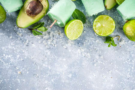 Homemade avocado ice creams. Vegan non-dairy ice cream. Avocado,lime and coconut healthy ice creams on grey stone background with fresh lime slices, avocados and ice.