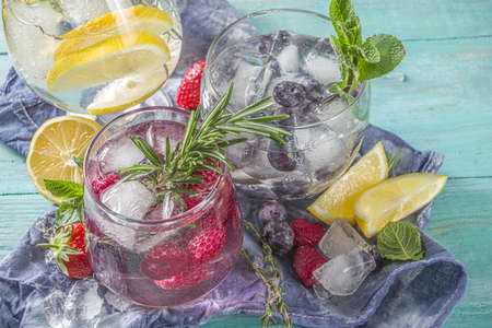 Summer cold drink concept. Fruit and berries gin tonic cocktail, or infused water lemonade mocktails, with fresh blueberry, raspberry, lemon and herbs, blue green old wooden background copy space Archivio Fotografico