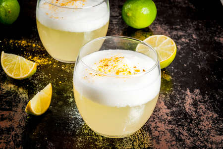 Peruvian, Mexican, Chilean traditional drink pisco sour liqueur, with fresh lime, on rusty black table, copy space