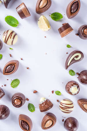 Various chocolate candies over white background. Different sweet and chocolates with mint leaves, copy space, simple pattern layout