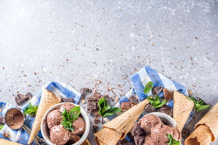 Homemade chocolate ice cream with chocolate pieces and shavings, and ice cream cones. In small white bowls on white grey stone table copy space Stockfoto