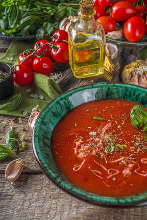 Summer homemade cold tomato cream soup. Fresh gazpacho, tomato puree soup with parmesan cheese, garlic, basil. On a wooden rustic background with spices and tomatoes.