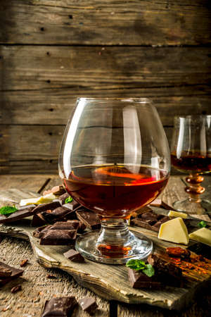 Strong alcohol drink. Glass of brandy, whiskey or cognac on the wooden table Archivio Fotografico