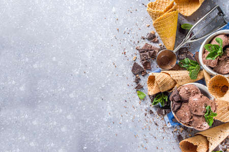 Homemade chocolate ice cream with chocolate pieces and shavings, and ice cream cones. In small white bowls on white grey stone table copy space
