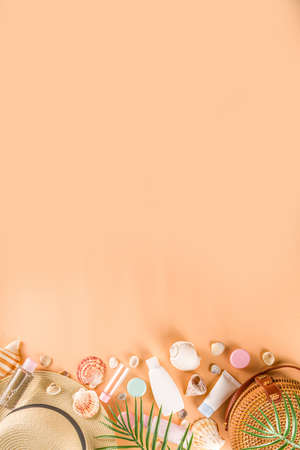 Summer cosmetics background. Summer skincare, sunscreen cosmetics, travel kit miniatures flat lay. Trendy peach background, with women bag, sea shells, tropical leaves, straw hat. Copy space above