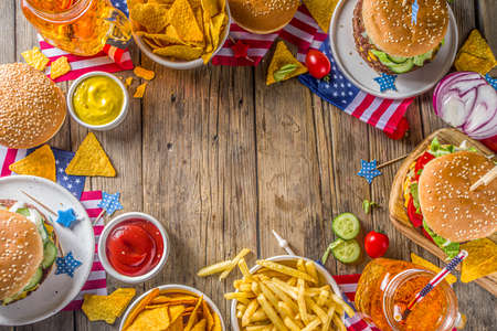Celebrating Independence Day, July 4. Traditional American Memorial Day Patriotic Picnic with burgers,  french fries and snacks, Summer USA picnic and bbq concept, Old wooden background  Stock Photo