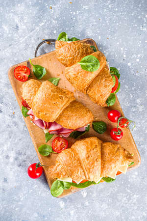 Homemade croissant sandwiches with ham, cheese, fresh vegetables and herbs, Standard-Bild