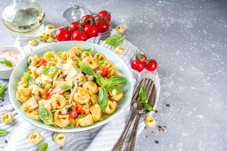 Italian ravioli, tortellini pasta with parmesan cheese and vegetables - spinach, tomatoes, mushrooms and basil, On grey stone background copy space