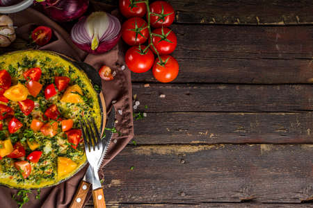 Homemade rustic style frittata. Frittata with spinach, cheese and tomato in skillet. Wooden background with vegetables copy space Standard-Bild