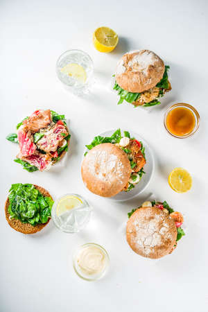 Various seafood and fish burgers assortment. Homemade healthy burger with grilled prawn, salmon, tuna, sea bass, fresh herbs, mozzarella cheese and baby spinach.  Stock Photo