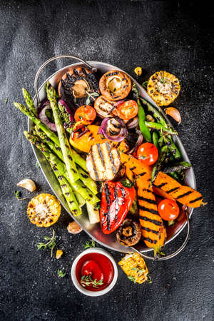 Hot vegetable salad. Set different grilled vegetables on a plate. Vegan barbeque picnic set, with asparagus, tomatoes, mushrooms, peppers, corn and sauces 스톡 콘텐츠