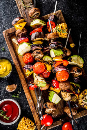 Vegan barbecue party fest concept. Whole vegetable diet kebabs set of various vegetables on skewers. Grilled vegetables on skewers - zucchini, tomato, pepper, eggplant, mushrooms, with sauces 스톡 콘텐츠
