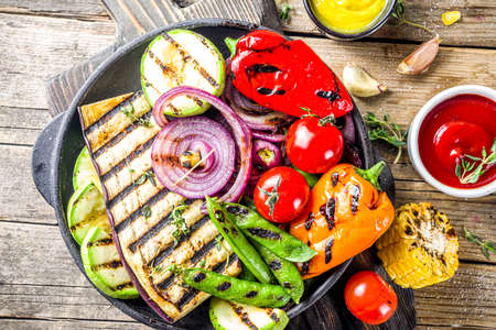 Hot vegetable salad. Set different grilled vegetables on a plate. Vegan barbeque picnic set, with asparagus, tomatoes, mushrooms, peppers, corn and sauces