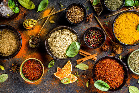 Set of Spices and herbs for cooking. Small bowls with colorful seasonings and spices - basil, pepper, saffron, salt, paprika, turmeric. On black stone table top view copy space Zdjęcie Seryjne