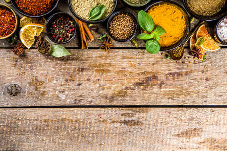 Set of Spices and herbs for cooking. Small bowls with colorful  seasonings and spices - basil, pepper, saffron, salt, paprika, turmeric. On rustic wooden plank table background, top view copy space Фото со стока