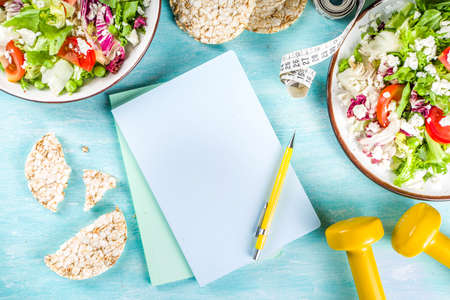 Healthy eating, slimming. dieting and weigh loss concept background. Fresh greenery summer salad with fruit, measuring tape, dumbbells and diet plan dairy notepad, flat lay above copy space