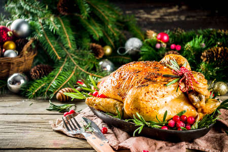 Traditional Christmas and Thanksgiving roasted whole chicken with fruit and rosemary. Rustic wooden christmas table, with xmas tree branches and decorations copy space