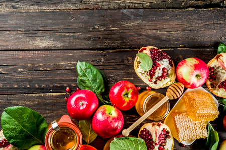 Jewish Autumn Rosh Hashana celebration. Traditional products for the celebration of Rosh Hashanah - apples with leaves, pomegranate, honey, honeycombs, wooden background